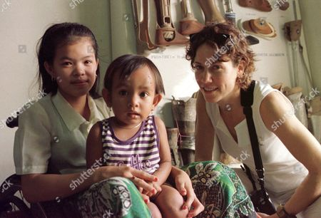 SHERYL CROW American music star Sheryl Crow, right, poses with two Cambodian polio victims in front of a display of prosthetic limbs at a rehabilitation center run by Veterans International Monday, Jan.17, 2000. Sheryl Crow began a tour of Cambodia with Veterans International Monday with fellow singer Nanci Griffith as spokespersons for the International Campaign to Ban Land Mines