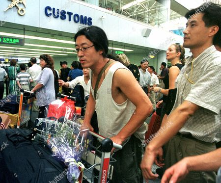 Stock Image of BEI LING Bei Ling, center wearing glasses, a U.S.-based editor of a dissident literary magazine, waits in line for a flight to San Francisco at the Beijing Airport as a plain clothed policeman, right, keeps watch. Chinese police released Bei after 16 days in custody and sent him back to the United States