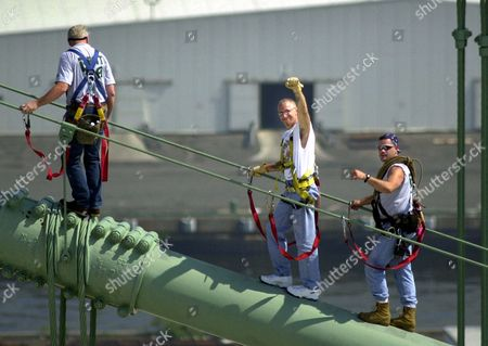 "Stock Photo of CROCE Philadelphia 76ers team President Pat Croce, center, and two unidentified members of his crew scale the Walt Whitman Bridge to hang a 5-feet by 70-feet ""GO SIXERS BEAT L.A."" banner across the bridge, in Gloucester, N.J"
