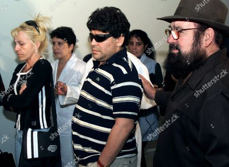 Diego Maradona, center, walks with his wife Claudia Villafane, left, and Cuban Dr. Bernabe Ordaz upon his arrival to the Havana airport . The former Argentine soccer star is in Cuba to begin a drug rehabilitation program