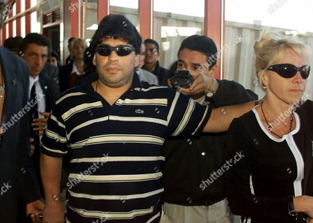 Diego Maradona, left arrives at the Havana airport, with his wife, Claudia Villafane, right. The former Argentine soccer star arrived Tuesday morning in Cuba to be treated for drug abuse after a hospitalization in his homeland that was brought on by cocaine use