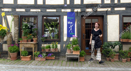 MUELLER TO GO WITH STORY TITLED EURO COUNTDOWN--Petra Mueller, walks out of the flower shop she owns in Michelstadt, Germany, . As the final six-month countdown to the currency switch begins, shop owners are heading into a tricky transition, especially during the first several months of 2002 when customers will still be able pay in old national currencies, but stores will have to give change in euros. That means cashiers will have to calculate the exchange rate on every transaction