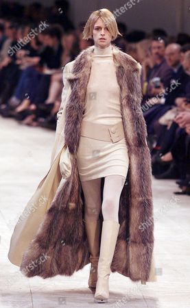 Stock Image of CERRUTI A model sports a fur-lined coat over a beige belted short dress with matching boots by American-Greek designer Peter Speliopoulos for Cerruti during his fall-winter ready-to-wear fashion show presentation in Paris