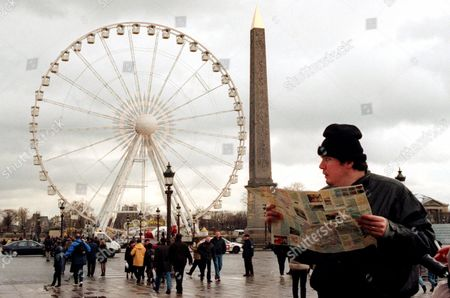 An unidentified tourist walks with a Paris map near a giant ferris wheel and the Obelisk on the Concorde Plaza in Paris, France . Paris has been battered by fierce storms which caused the swollen Seine River to flood riverside roads and walkways in several parts of the city. Paris Mayor Jean Tiberi said urgent repair work would be done quickly, and predicted that millennium parties in the city, expected to draw millions of revelers, would not be disrupted