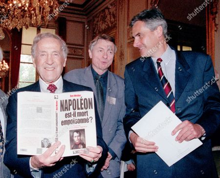 """Canadian doctor Ben Weider, left, President of the International Napoleonic Society, displays his book """"Was Napoleon poisoned ?"""", at the French Senate after a presentation to members of the Society and the media of results of the research monitored by Scotland Yard and the FBI about an alleged death by arsenic poisoning of the French emperor. Weider's conclusions tend to confirm this assumption, leading to an investigation for murder with a possible presentation of a formal case to the Crown Prosecution Service. Prince Charles Napoleon, right, descendant of Napoleon's younger brother Gerome, and Prince Joachim Murat, descendant of Marshal of France Joachim Murat, look on"""