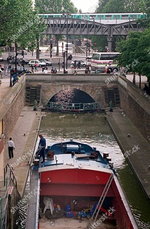 CANALS A barge waits at a lock on the Canal Saint-Martin in Paris . Paris Mayor Jean Tiberi unveiled Wednesday a 600 million francs ($85.7 million) plan to make the historic waterways of the French capital tourist-friendly, with new boat trips along the 180 kilometer long (81 mile) waterways, renovated quays and high-tech lighting