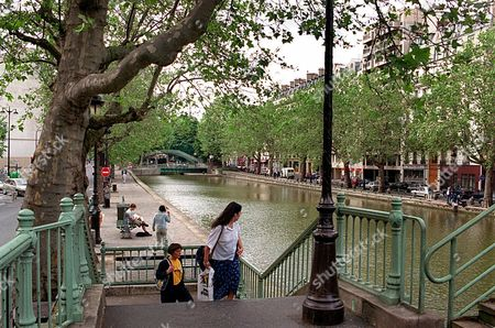 CANALS Parisians walk along the Canal Saint-Martin in Paris . Paris Mayor Jean Tiberi unveiled Wednesday a 600 million francs ($85.7 million) plan to make the historic waterways of the French capital tourist-friendly, with new boat trips along the 180 kilometer long (81 mile) waterways, renovated quays and high-tech lighting