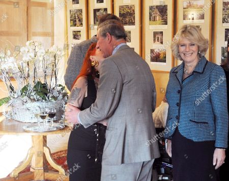 Prince Charles receives a kiss from Linda Taylor with Camilla, Duchess of Cornwall looking on