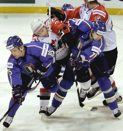 BREWER Italy's player Scott Beattie, left, and Lino de Toni, right, challenge Canada's Eric Brewer, center, from Edmonton Oilers and an unidentified player, back, during their Group D match at the World Icehockey Championhips Canada versus Italy in Hanover, northern Germany, on