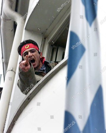 DEMONSTRANT Beside a Greek flag, right, a Kurdish demonstrator shouts out of a window of the Greek consulate in Frankfurt, Germany,, when Kurdish demonstrators protest against the arrest and extradition to Turkey of fugative Kurdish rebel leader Abdullah Ocalan. In a Europewide action Kurds occupied Greek embassies and consulates to demand Ocalans release