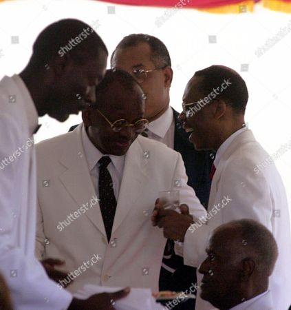 ARISTIDE PAUL Haitian President Jean-Bertrand Aristide, right, speaks to Minister of Culture Guy Paul during a flag day ceremony in Arcahaie, Haiti on . Aristide on Friday held out an olive branch to the opposition but stopped short of saying he would give in to their demand for new elections