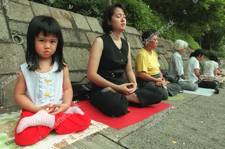 FALUN GONG FOLLOWERS May Kwok, left, a 3 1/2 old follower of the meditation group Falun Gong, joins in a meditation exercise outside the mainland Chinese-run Xinhua news agency in Hong Kong . About 30 followers of the group partook in a protest outside China's de facto embassy in Hong Kong after authorities in Beijing banned the group in mainland China