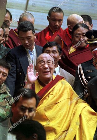Stock Image of DALAI LAMA KARMAPA His Holiness the Dalai Lama waves to supporters as he leaves the ceremony in his honor marking the 60th anniversary of his enthronement in Dharmsala, India. Surrounding the 64-year-old Buddhist leader are the four high Lamas who participated in the ceremony, including at background center, the 17th Karmapa Lama, Urgyen Trinley Dorje