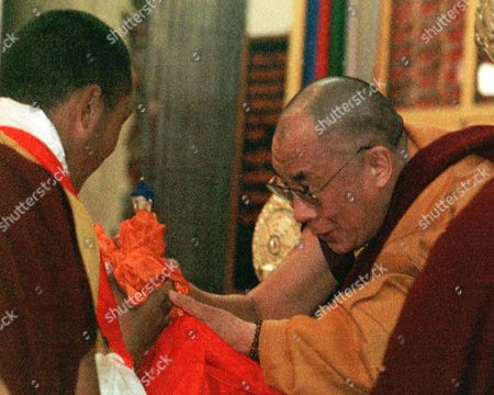 Stock Photo of DALAI LAMA KARMAPA The Dalai Lama, right, hands the 17th Karmapa Lama, Urgyen Trinley Dorje, a blessed Kota during a ceremony to mark the 60th anniversary of the Dalai Lama's enthronement in Dharmsala, India. Thousands of Tibetans travelled from across India, Nepal and China to attend Friday's ceremony. It was the pair's first joint appearance since the Karmapa fled Chinese-controlled Tibet recently