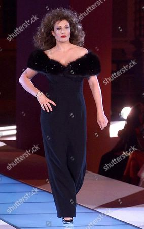 LE BROCK American actress Kelly LeBrock wears an evening black dress, bordered in black fox fur, by Italian fashion designer Gai Mattiolo at fall-winter high fashion show in Rome