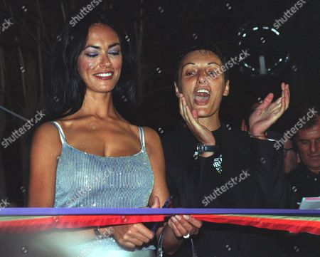 """CUCINOTTA BATTAGLIA Italian actress Maria Grazia Cucinotta, left, and the president of the Italian """"Mario Mieli"""" gay rights association, Imma Battaglia, the cut a """"rainbow"""" ribbon to mark the official start of the World Gay Pride 2000 celebrations, in Rome. A group of neo-fascists from Forza Nuova (New Force) protested Saturday againt the weeklong festival celebrating gay, lesbian, bisexual and transgender life"""