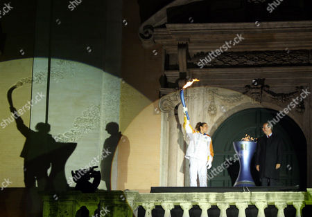 Olympic torchbearer Elisa Santoni, left, holds up her torch after lighting the Olympic flame as Rome's Mayor Walter Veltroni smiles, at Rome's Campidoglio Capitol Hill, in the opening stages of the Turin 2006 Winter Olympic Flame tour of Italy, .The flame is planned to cover 11,300 kilometers (7,022 miles) throughout Italy involving 10,000 torchbearers, gondolas, a Ferrari sports car and a cavalry regiment before arriving in Turin for the opening ceremony on Feb. 10th