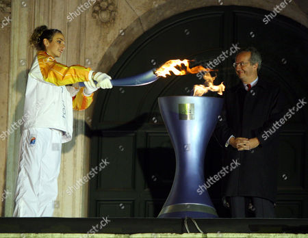 Olympic torchbearer Elisa Santoni, left, lights the Olympic flame with her torch as Rome's Mayor Walter Veltroni smiles, at Rome's Campidoglio Capitol Hill, in the opening stages of the Turin 2006 Winter Olympic Flame tour of Italy, .The flame is planned to cover 11,300 kilometers (7,022 miles) throughout Italy involving 10,000 torchbearers, gondolas, a Ferrari sports car and a cavalry regiment before arriving in Turin for the opening ceremony on Feb. 10th