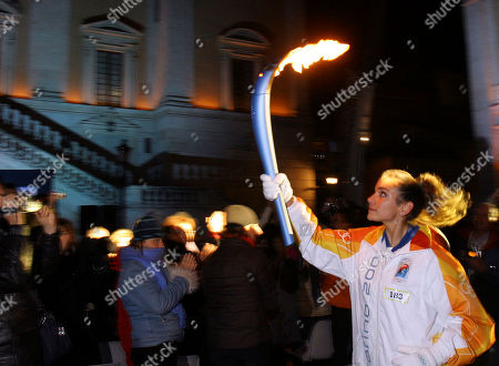 Olympic torchbearer Elisa Santoni, runs with her torch as she arrives at Rome's Campidoglio Capitol Hill, in the opening stages of the Turin 2006 Winter Olympic Flame tour of Italy, .The flame is planned to cover 11,300 kilometers (7,022 miles) throughout Italy involving 10,000 torchbearers, gondolas, a Ferrari sports car and a cavalry regiment before arriving in Turin for the opening ceremony on Feb. 10th