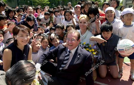 MOORE THOLSTRUP CHAN Roger Moore, British actor and a goodwill ambassador for UNICEF, center, accompanied by his Danish girlfriend Christina Tholstrup, behind Moore, and Japan Committee for UNICEF Ambassador Agnes Chan, left, is surrounded by Japanese children during his visit to Yotsuya Dairoku Elementary School in Tokyo Monday morning, . Moore is currently in Tokyo to raise Japanese attention to the 2nd World Congress against Commercial Sexual Exploitation of Children scheduled to be held in Yokohama in December