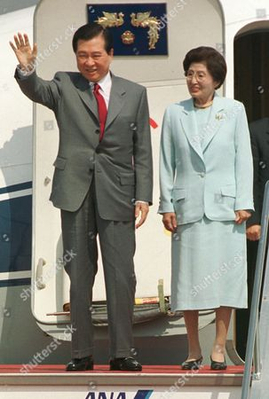 KIM LEE South Korean President Kim Dae-jung waves upon his arrival at Tokyo International airport, . Kim arrived for a three-day visit to meet Japanese leaders to discuss warming ties with North Korea and expanding relations with Japan. Accompanied Kim at right is his wife Lee Hee-ho