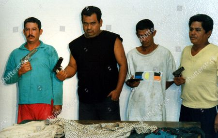 """MEXICO CAMPOS KIDNAPPERS From left Juilan Cebrero Castro alias """"El Guero"""", Vicente Garcia Rios, Enoel Parra Vargas alias """"El Flaco"""" and Jose Morales Garcia alias """"El Profe"""" are presented with their weapons at police headquarters in the resort town of Acapulco, Guerrero state, Mexico . Prosecutors announced Thursday that the four men have been arrested and face up to 40 years in prison each after confessing to kidnapping the father of star Mexican soccer goalie Jorge Campos"""