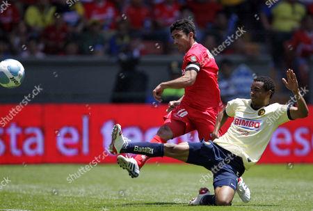 Antonio Naelson Zinha, Adolfo Rosinei Toluca's Antonio Naelson Zinha, left, kicks the ball to score as America's Adolfo Rosinei, of Brazil, defends at a Mexican soccer league match in Toluca, Mexico