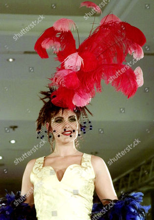 """HUT An unidentified model sports a giant hat with red feathers on the catwalk of the Intercontinental Hotel in Berlin, . The fashion show """"Pompoes"""" (pompous) displays the work of German designer Harald Gloeckler"""