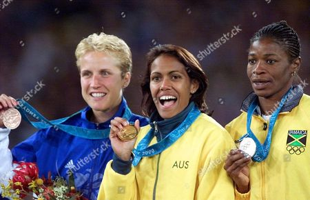 MERRY FREEMAN GRAHAM Gold-medalist Cathy Freeman of Australia, center, silver-medalist Lorraine Graham of Jamaica, right, and bronze-medalist Katharine Merry of Great Britain, hold up the medals they won in the 400-meter race at the Summer Olympics, at Olympic Stadium in Sydney