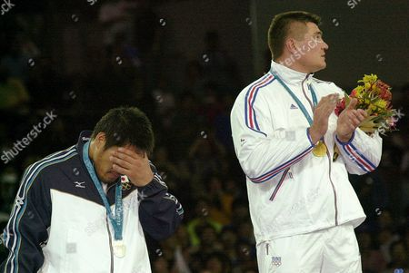 Stock Picture of SHINOHARA, DOUILLET Japan's Shinichi Shinohara, left, covers his face as France's David Douillet applauds on top of the medal stand after their over-100 kg judo competition at the Summer Olympic Games in Sydney . Douillet defeated Shinohara to win the gold medal
