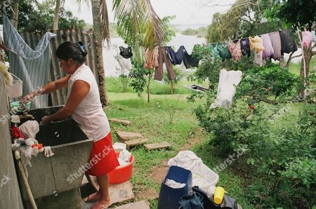 Stock Image of An unidentified woman who lives in the watershed of the Panama Canal washes her cloths, in Arenosa, 70 kilometers (43 miles) from Panama City, Panama . Canal officials have doubled the size of the canal's watershed this year, but increased urbanization of surrounding areas and projected traffic increases threaten the precious water supply. Inhabitants of the watershed are given seminars by canal authorities to prevent damage to the water supply. (AP Photo/Tomas van Houtryve