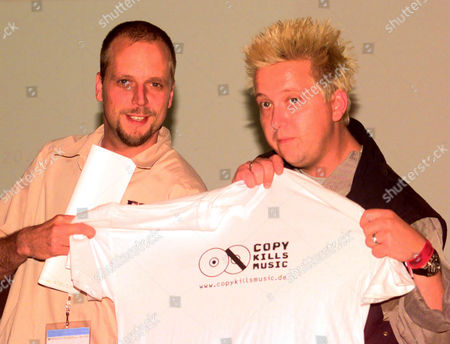 """SMUDO KRUMBIE German musicians Smudo, left, of """"Die Fantastischen Vier"""" and Sebastian Krumbiegel of """"Die Prinzen"""" show a t-shirt, as they start the campagne """"Copy kills Music"""" against the illegal copying of music during a news conference at the Popkomm fair in Cologne, . It is a campagne of the music industry and some musicians"""