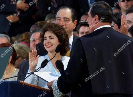 CALDERON GARCIA KRANS Sila Calderon, left, raises her right hand as she is sworn is as Governor of Puerto Rico by Judge Jose Antonio Andreu Garcia, right, during inauguration ceremonies at the Capitol building in San, Juan, Puerto Rico . At center is Calderon's husband Adolfo Krans