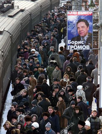 Commuters move past an election billboard of Moscow gubernatorial candidate Boris Gromov, at Belarus railway station in Moscow, . Russian parliamentary and local elections are scheduled for Sunday