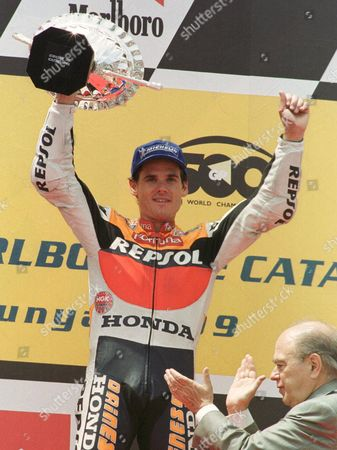 CRIVILLE Spain's Alex Criville lifts the trophy as he is applauded by Jordi Pujol, president of the Autonomous Government of Catalunya, after Criville won the 500cc class race of the Motorcycling Grand Prix of Catalunya Sunday, June 20,1999 in Barcelona's Montmelo circuit