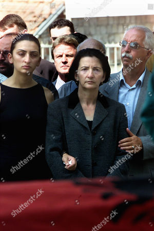 Donika Luci, center, wife, and Njomza, the daughter, left, of Rexhep Luci, director of Kosovo's planning and reconstruction department who was killed on Monday night in front of his apartment in Kosovo's capital Pristina, during a funeral ceremony joined also by U.N. top official Bernard Kouchner, backround center left, on . Luci, a well known Pristina architect was in charge of clamping down on illegal constructions. The first demolition orders were issued last month