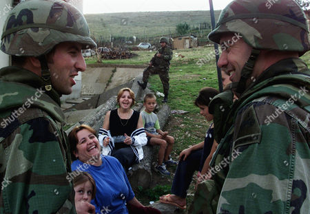 Sgt 1st Class Mark Hoffman, 34 (left) from Beachwood, New Jersey and his translator share a joke with local Albanian women and children during their daily patrol through the ethnically mixed village of Novo Brdo on . U.S soldiers came to Kosovo expecting combat, but their true mission in this province is peacekeeping and helping the locals with day-to-day problems