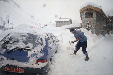 Michael Pollard of Melbourne, Australia, tries to dig his car out after another heavy snowfall in Val-Isere, France on . Strong winds reaching 80 mph (130 km per hour) swept over the Alpine peaks overnight and an additional 16 inches (40 centimeters) of snow fell causing some changes in Olympic events on Monday