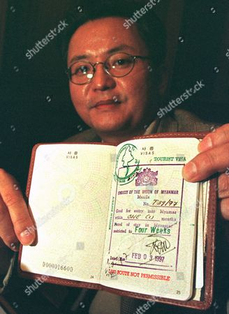 KIM SANG WOO South Korean lawmaker Dr. Kim Sang-woo shows his passport with a valid Burmese visa during a press conference in Bangkok . Kim was refused entry into Burma and forcibly ejected by officials on Thursday. Kim said he was making his trip to find out first hand about Burma's political situation and hoped to meet National League for Democracy Leader Aung San Suu Kyi