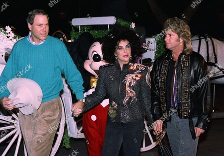Actress Elizabeth Taylor is joined by husband Larry Fortensky, right, and Disney President Michael Eisner after arriving at her 60th birthday party at night on at Disneyland in Anaheim, Calif