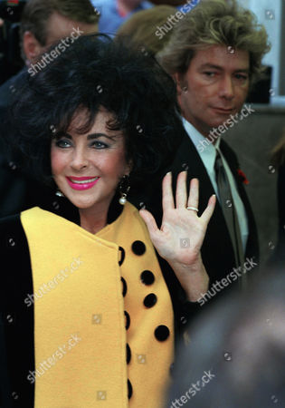 Actress Elizabeth Taylor waves to crowds in morning on after arriving at a London restaurant for lunch with her husband Larry Fortensky, in background. The couple was married on Michael Jackson's estate last month