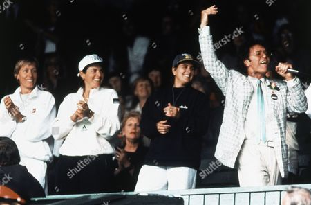 Veteran British singer Cliff Richard, accompanied by a chorus of tennis stars, including, from left, nine-times champion Martina Navratilova, Gigi Fernandez and 1994 champion Conchita Martinez, entertains the crowd on the Centre Court at Wimbledon, London, while rain held up the Men's Singles quarter-final between Pete Sampras and Richard Krajicek, unseen