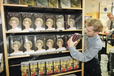 "A London bookstore employee puts the first copies of ""Princess in Love"" by Anna Pasternak on display in London on . The book is the story of Maj. James Hewitt, who claims he had an affair with the estranged wife of the heir to the British throne"