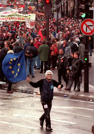 A member of the French communist party wearing a mask of socialist Prime Minister Lionel Jospin runs waving a European flag during a demonstration in Paris . French Communist Party leader Robert Hue called Sunday for a referendum on the single European currency and for the European Union to make jobs and social issues its priority. Hue linked the fate of the unemployed in France - where there is a 12.4 percent jobless rate - to the European currency, the euro, to be introduced starting next year