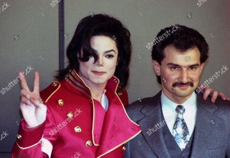 "US pop star Michael Jackson flashes the victory sign while embracing Saudi Prince Al-Waleed Bin Talal Bin Abdulaziz Al Saud, right, after signing agreements to form a new joint venture called ""Kingdom Entertainment"" in Paris, France, on"