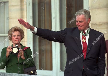 HESTON US movie star Charlton Heston waves to photographers while his wife Lydia Clarke takes pictures after he was named Commander in the Arts and Letters Order at the French culture ministry in Paris . The Hestons also celebrated their 53rd anniversary of marriage Monday