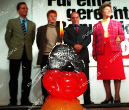 A candle caricature of German Chancellor Helmut Kohl burns infront of the top Berlin candidates from left: Manfred Mueller, Petra Pau, Gregor Gysi, and Christa Luft, of the Party for Democratic Socialism (PDS) during the final rally of the PDS in Berlin s destrict Mitte
