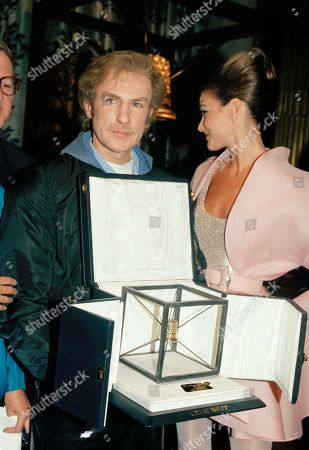 French designer Claude Montana of the Lanvin fashion house shows the Golden Thimble Award he just received for the best 1991 Spring-Summer Haute Couture collection in Paris, . He was also awarded last July 26,1990 for his Fall-Winter Haute Couture Collection. Unidentified model at right
