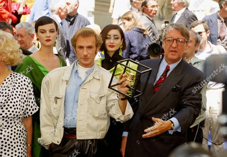 French designer Claude Montana of the Lanvin fashion house shows the Golden Thimble Award the prize for the best 1990-91 Fall Winter Haute Couture collection he won in Paris, . Behind him are two of his models