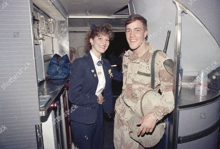 Pan Am flight attendant Christine Achillo of Atlanta greets Pfc. Paul Nelson of Ft. Worth, Texas on board a Pan AM 747 at Dhahran airport on before the plane took off for Ft. Hood in Texas. Achillo, who flew Nelson, a member of the army?s 1st Calvary Division, to Saudi Arabia in August, kept her promise that she would be back to pick up take him home
